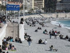 People sit on the beach of the Promenade des Anglais in Nice